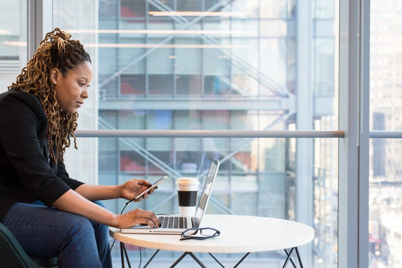 woman-holding-smartphone-sitting-in-front-of-laptop-on-table-1181255